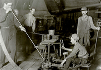 Photograph of glass blower and mold boy
